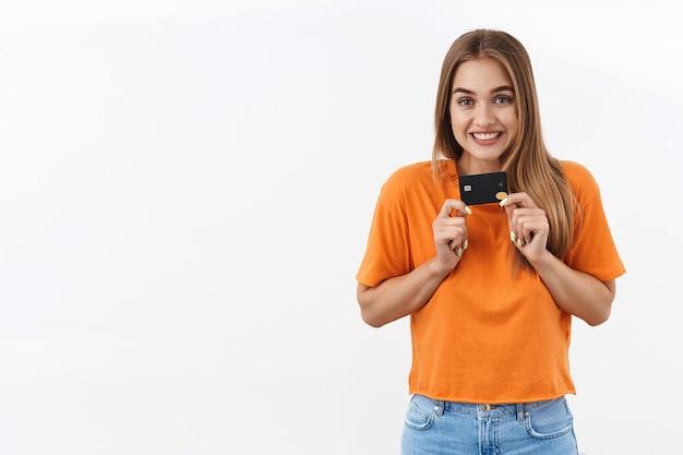 幸せな、興奮した金髪の魅力的な女の子は買い物、オンラインでの購入、インターネットでの買い物を待つことができません