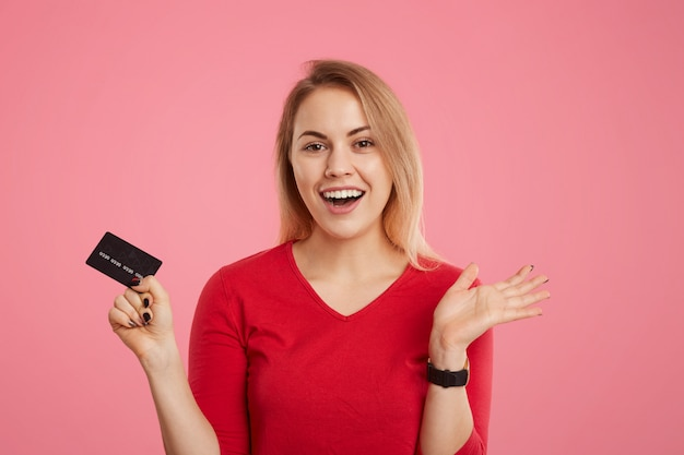 Happy excited blonde female holds plastic card, doesn't expect to receive salary, going to make payments, looks joyfully into camera