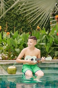 Happy excited boy sitting on edge of swimming pool, drinking coconut cocktail and playing on ukulele
