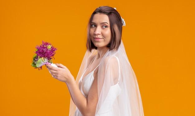Sposa felice ed eccitata in un bellissimo abito da sposa che sta per lanciare un bouquet di fiori da sposa
