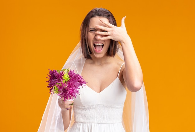 Happy and excited bride in beautiful wedding dress with wedding flower bouquet screaming covering eyes with palm