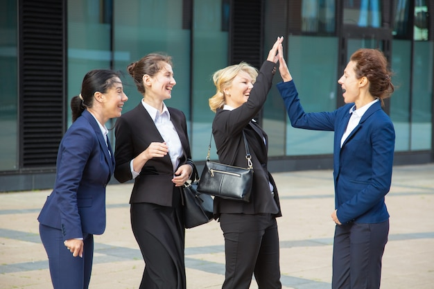 Happy excited business ladies giving high five. businesswomen wearing suits meeting in city, celebrating success. team success and teamwork concept