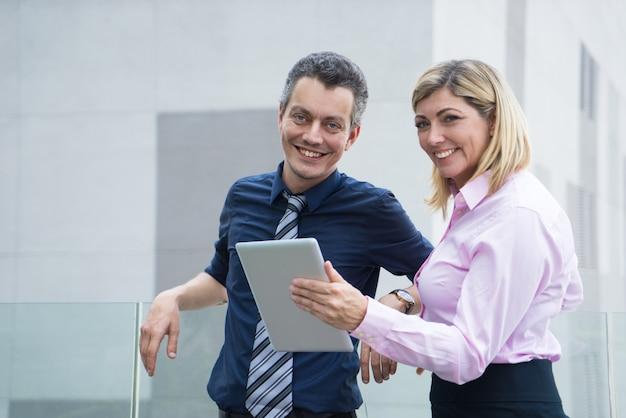 Счастливый возбужденных деловых людей, глядя на камеру и стоя на крыше офисного здания.