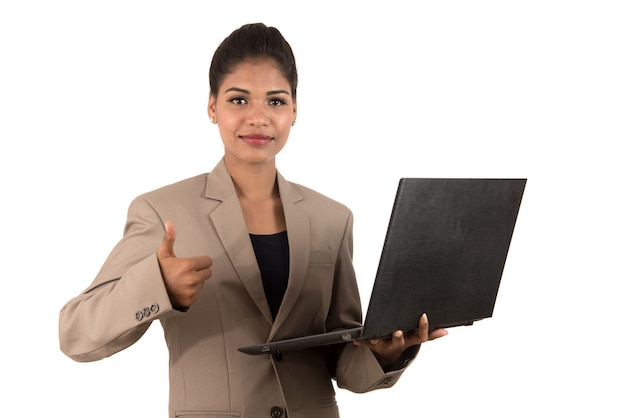 Счастливая взволнованная деловая женщина, держащая ноутбук и показывающая большие пальцы руки вверх изолирована на белом фоне
