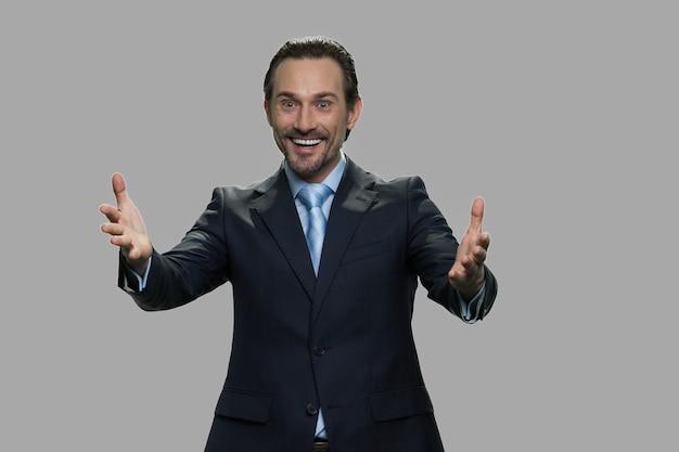 灰色の背景に幸せな興奮した実業家。興奮して手を上げる魅力的な成熟したビジネスマン。勝利を喜び、祝う。