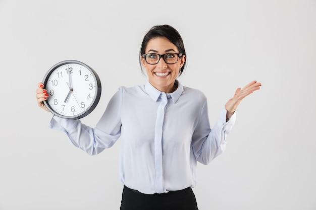 幸せな興奮した実業家は、目覚まし時計を表示して、白い壁の上に孤立して立ってスマートな服を着て
