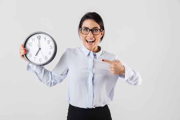 Happy excited businesswoman smartly dressed standing isolated over white wall, showing alarm clock