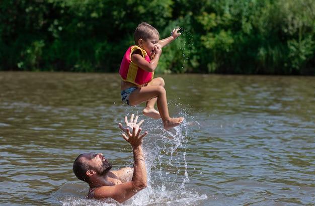 Счастливые взволнованные кавказские отец и сын плавают и прыгают в воду. семейный отдых. водные виды спорта.