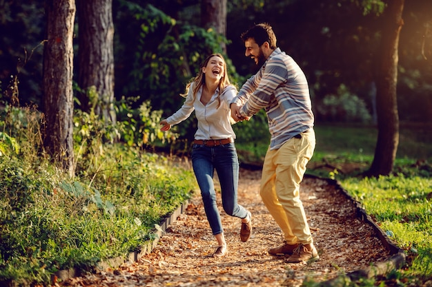 Happy excited caucasian young couple running on trail in woods and having good time. man holding woman's hand. adventure in nature concept.