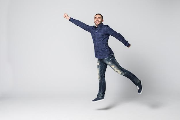 幸せな興奮して陽気な若い男がジャンプし、白い背景で隔離の成功を祝う
