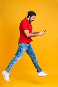 Счастливый возбужденный веселый молодой человек прыгает и празднует успех, изолированные на желтом фоне. с помощью телефона.