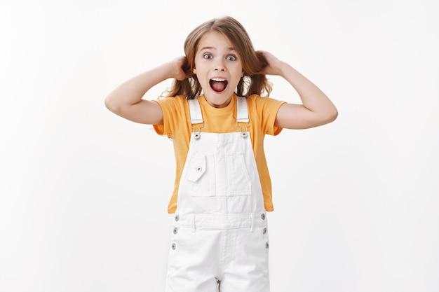 Счастливый взволнованный ребенок веселится, стоит игриво и удивлен, девушка трогает волосы, поднимает стрижку в воздухе, кричит, веселится и радостно, выражает восторженное веселое настроение, стоит у белой стены