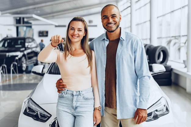 Happy excited couple or family buying a new car and showing keys