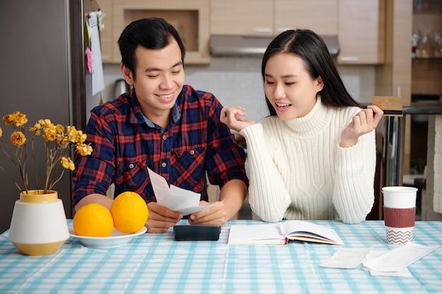 행복한 흥분된 부부는 가계 예산을 관리하고, 플래너에 작성하여 수입과 지출을 추적합니다.