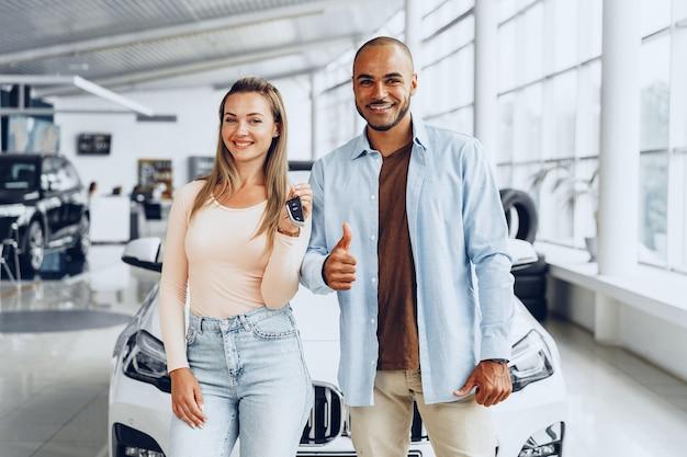 新しい車を購入し、鍵を見せて幸せな興奮したカップルや家族