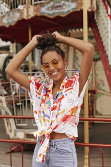 Felice eccitata donna bruna riccia in pantaloni di jeans, elegante camicetta colorata ritagliata e occhiali da sole arancioni tocca i capelli, sorride e posa vicino alla giostra