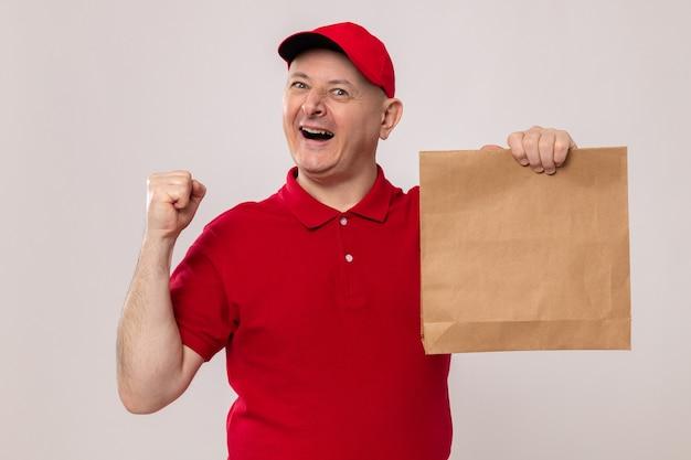 Felice ed eccitato fattorino in uniforme rossa e berretto che tiene il pacchetto di carta guardando la telecamera sorridendo allegramente pugno serrato in piedi su sfondo bianco