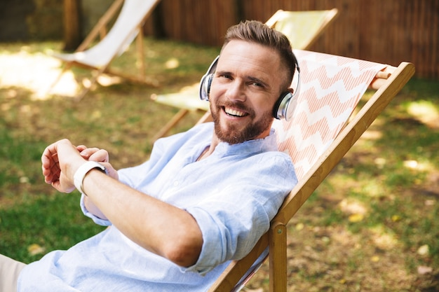 Happy excited emotional young bearded man listening music with headphones.