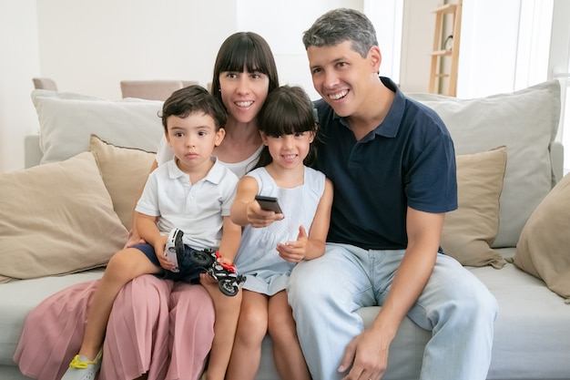 Happy excited family couple and two kids watching tv together, sitting on couch in living room, using remote control.