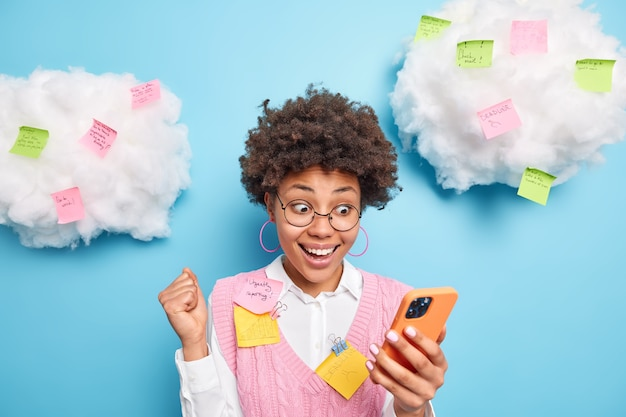 Happy excited female student with afro hair clenches fist celebrates successfully finished report looks amazed at smartphone display surrounded by colorful sticky notes to remember all tasks