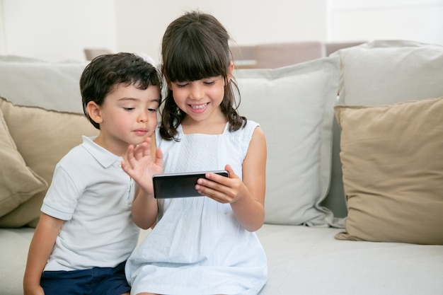 幸せな興奮している女の子と彼女の弟がリビングルームのソファに座っている間電話でオンラインゲームをプレイします。