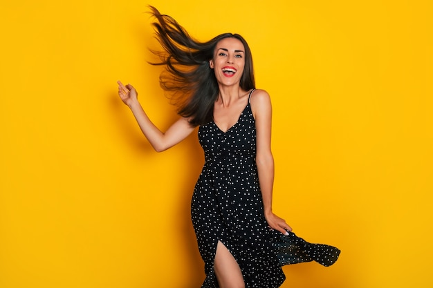 Happy excited gorgeous smiling brunette woman in a black summer dress is dancing isolated on yellow background and having fun