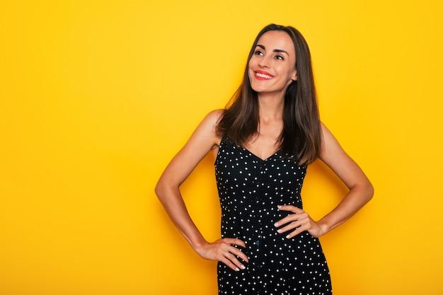 Счастливая возбужденная великолепная улыбающаяся брюнетка в черном летнем платье позирует изолированно на желтом фоне и веселится