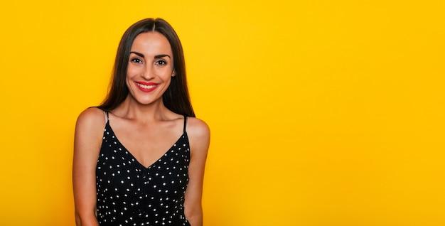 검은색 여름 드레스를 입은 행복한 흥분한 화려한 미소 브루네트 여성이 노란색 배경에 고립되어 포즈를 취하고 즐거운 시간을 보내고 있습니다