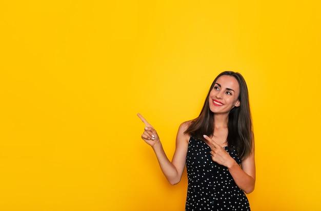 Счастливая возбужденная великолепная улыбающаяся брюнетка в черном летнем платье позирует изолированно на желтом фоне и указывая в сторону