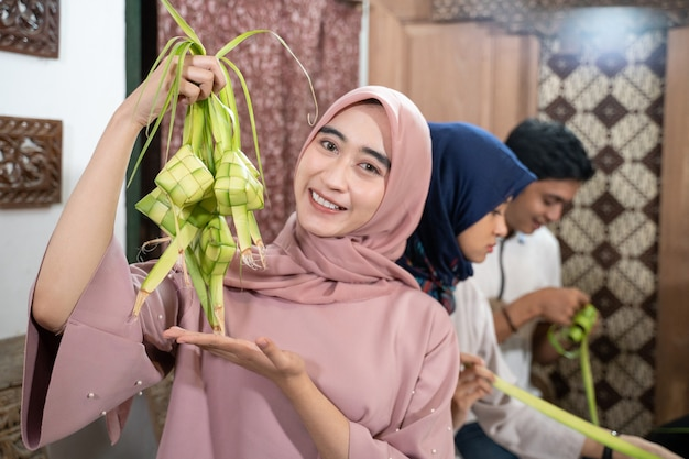Happy excited group of friend and family making ketupat together for eid fitr mubarak or idul fitri lebaran tradition