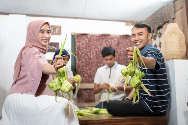 Счастливая взволнованная группа друзей и семьи, вместе готовящих кетупат для идул фитр мубарак или идул фитри лебаран традиции