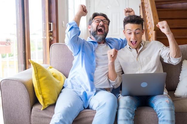 행복한 성장한 아들과 노트북을 사용하는 성숙한 50대 아버지, 성공을 축하합니다. 두 가족 세대의 스포츠 팬이 온라인 게임이나 컴퓨터로 경기를 관람하고 예스 승리 제스처를 만들고 재미를 즐깁니다.