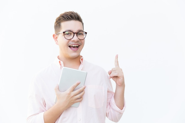 Happy excited guy in eyeglasses holding tablet