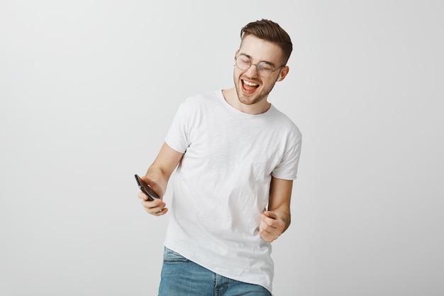 笑って、携帯電話を見て、ワイヤレスイヤホンで踊って幸せな興奮している男