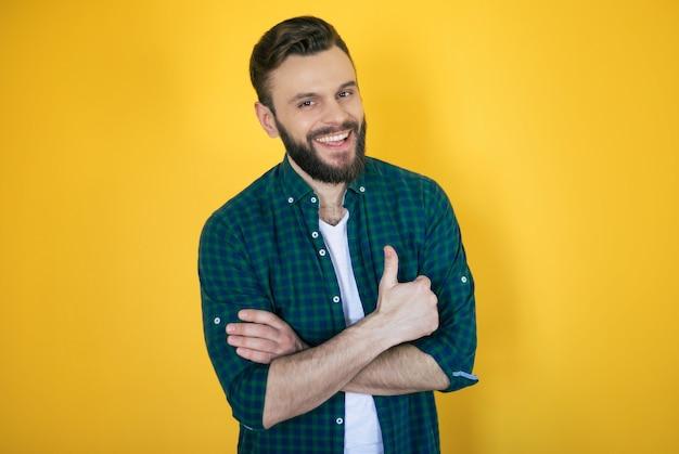 Счастливый возбужденный красивый бородатый современный мужчина в клетчатой рубашке позирует и показывает большой палец вверх