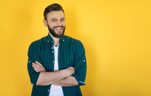 Счастливый возбужденный красивый бородатый современный мужчина в клетчатой рубашке позирует с широкой зубастой улыбкой