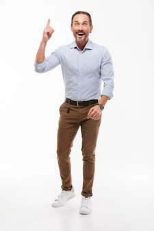 Happy excited handsome mature businessman have an idea pointing.