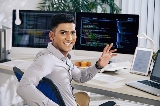 幸せな興奮したインドのソフトウェア開発者がオフィスの机に座って、振り返ってカメラに手を振る