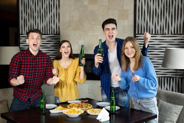 Счастливые возбужденные радостные четверо друзей смотрят футбол по телевизору в пабе, пьют алкогольные напитки и едят пиццу
