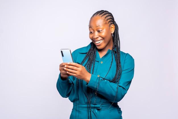 흰색 배경 뒤에 서 있는 스튜디오에서 휴대폰을 사용하는 행복한 흥분된 여성