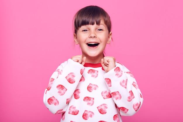 Счастливая взволнованная маленькая девочка сжимая кулаки, празднуя свой успех, глядя в камеру с возбужденными эмоциями, изолированными над розовой стеной.