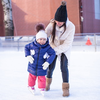 Happy excited little girl and her young mother learning ice-skating