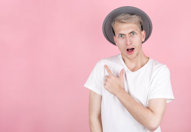 Happy excited man in hat pointing at copy space with finger isolated on pink background