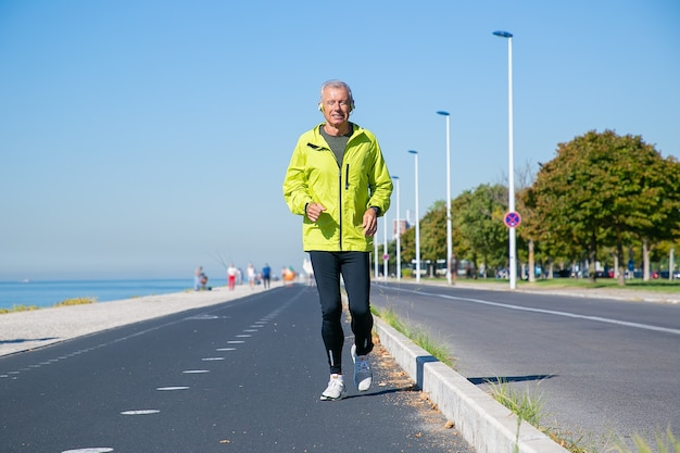 Happy excited mature man in wireless headphones jogging along river bank outside. senior jogger training for marathon. front view. activity and age concept