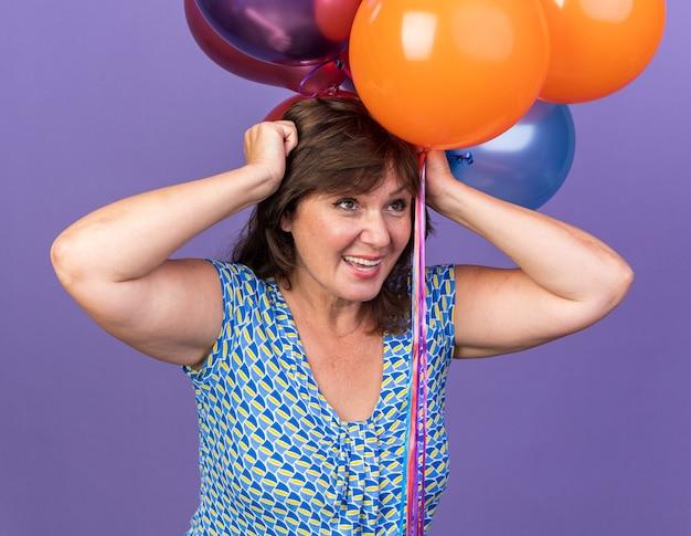 Felice ed eccitata donna di mezza età che tiene un mazzo di palloncini colorati che celebrano la festa di compleanno in piedi su un muro viola