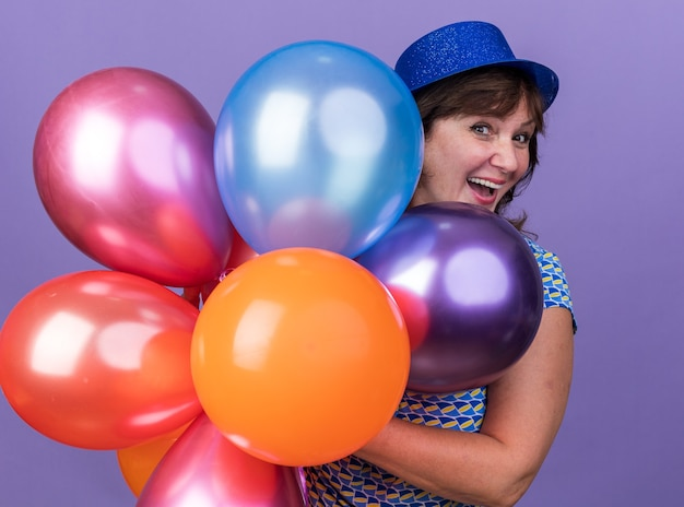 Felice ed eccitata donna di mezza età in cappello da festa con un mucchio di palloncini colorati che sorride celebrando la festa di compleanno in piedi sul muro viola