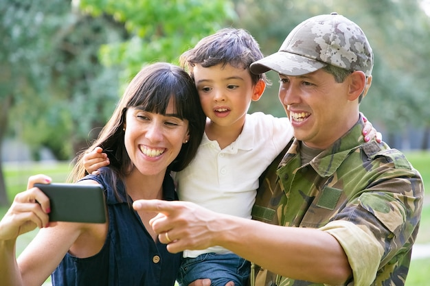 幸せな興奮した軍人、彼の妻と幼い息子が都市公園で携帯電話で自分撮りをしています。正面図。家族の再会または帰国の概念