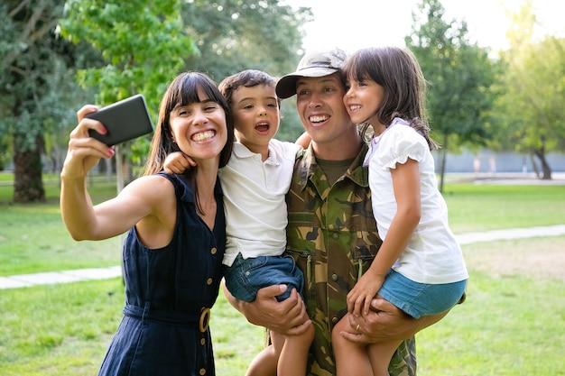 幸せな興奮した軍人、彼の妻と2人の子供が戻ってきたお父さんを祝い、公園で余暇を楽しんだり、携帯電話で自分撮りをしたりします。ミディアムショット。家族の再会または帰国の概念