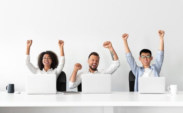 Счастливые возбужденные современные деловые люди с поднятыми руками празднуют успешное завершение проекта, сидя за столом, с ноутбуками в светлом офисе с белой стеной на заднем плане