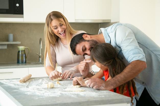 台所のテーブルで生地を作るように娘に教える間楽しんで幸せな興奮しているママとパパ。若いカップルと彼らの女の子が一緒にパンやパイを焼きます。家族の料理のコンセプト